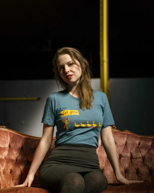 seated female model wearing graphic t-shirt indoors