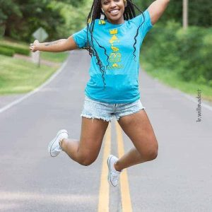 jumping female model wearing graphic t-shirt outdoors