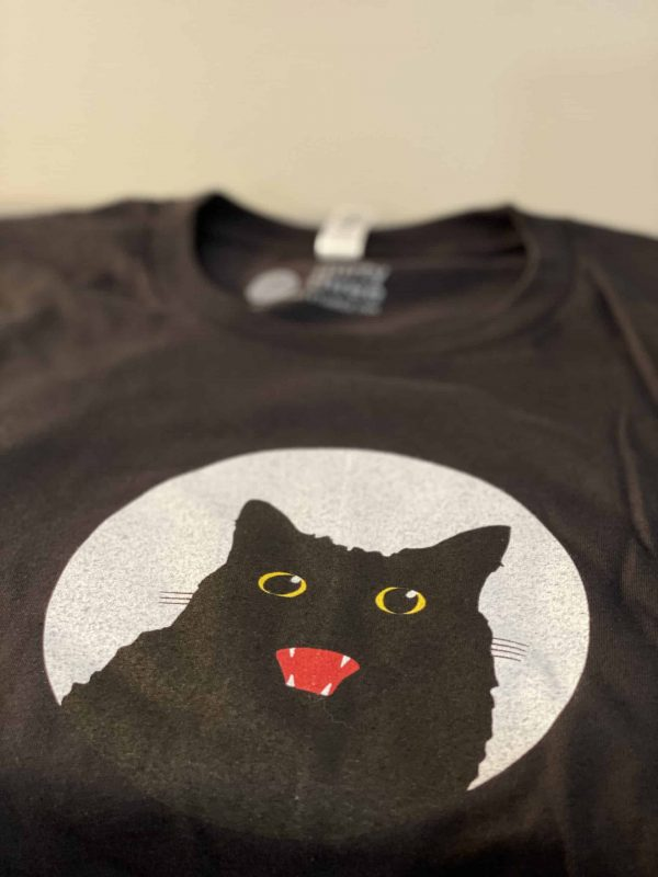 stack of black t-shirts with cat graphic