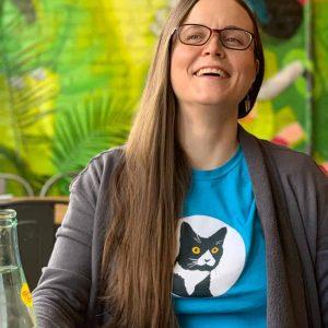 smiling female model wearing graphic aqua color t-shirt indoors