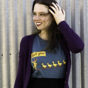 smiling female model wearing graphic t-shirt outdoors