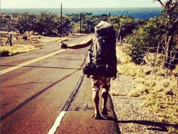 man hitchhiking on a desert road