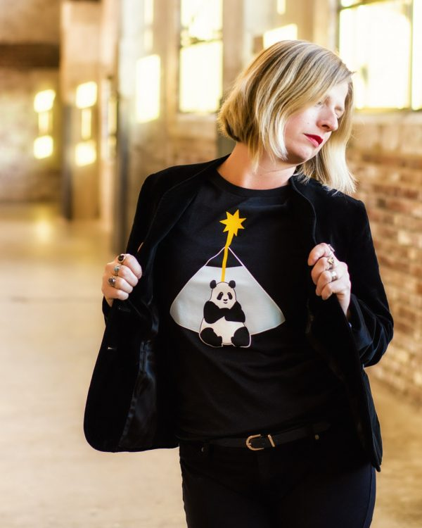 female model wearing black graphic tee and jacket indoors