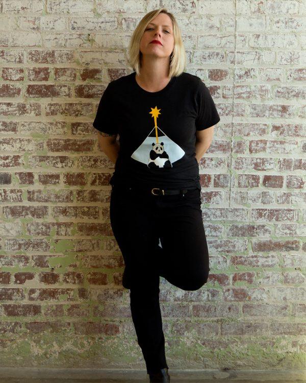 female model wearing black graphic tee indoors