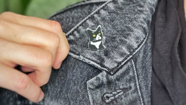 plastic daft cat pin on denim jacket